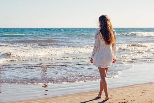 kobieta w białej sukience na plaży